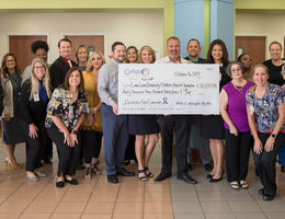 male and female staff and admin from both organizations pose with giant check