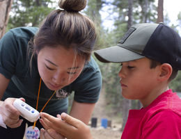 Amy Myung Song, a fourth year student at LLU School of Pharmacy, helps camper Cole Hoelker test his glucose level at Camp Conrad Chinnock on July 24.