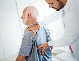physician checks elderly mans back for pain