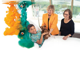 two women stand next to patient's bed giving him teddybear