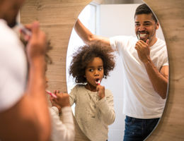 Father and daughter brush teeth in a mirror