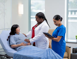 pregnant mom on bed being examined by female doctor and nurse