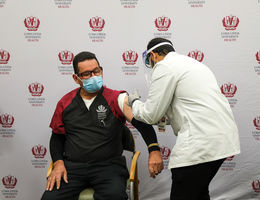 male hospital worker receives COVID-19 vaccine from male pharmacy student