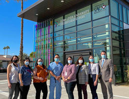 group of physicians and staff stand in front of clinic facility