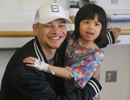 Country artist Kane Brown receives a hug from Children's Hospital patient Jennifer Nguyen.