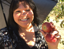 Regina Juarez smiles while holding apples picked from an apple orchard