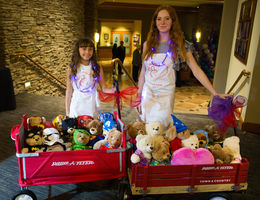 two young girls standing with red wagons full of teddybears