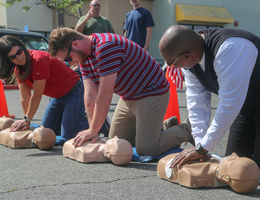three people learning hands-only CPR