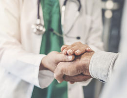 unidentified doctor holds hand of unidentified patient