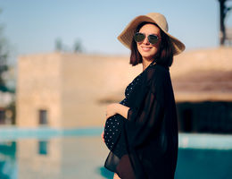 Pregnant Woman Relaxing on Vacation By The Pool