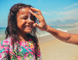 Little surfer girl preparing for surf with suntan lotion on a face