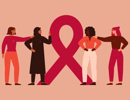 Four women of various races and ethnicities stand gathered around the breast cancer awareness ribbon