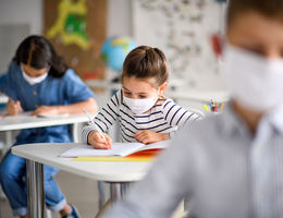 Small children with face mask back at school after covid-19 quarantine and lockdown, writing.