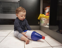 child sitting on the floor holding household chemical bottle from under the sink cabinetry