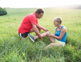 Male helping female with knee pain while hiking