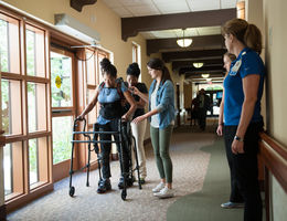 nurses help a patient walk in hallway with robotic assistance