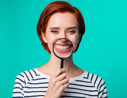 Woman holding a magnifying glass in front of teeth