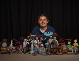 young man poses with claymation characters