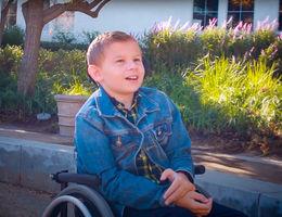 adolescent boy sitting outside in wheelchair