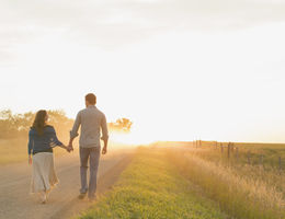 Couple walking toward a sunset on a dirt road