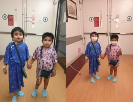 two young boys standing in hospital gowns holding hands