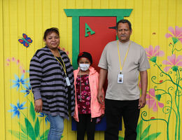 hispanic female pediatric patient poses for photo with her mother and father