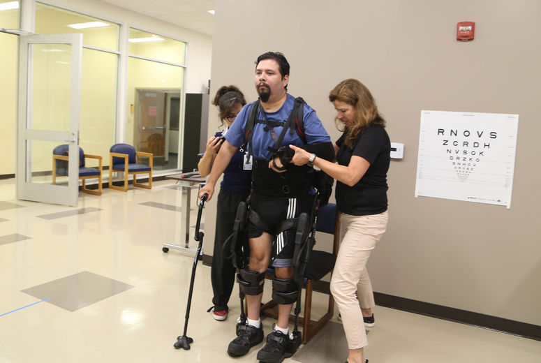 two medical assistants help man walk with machine