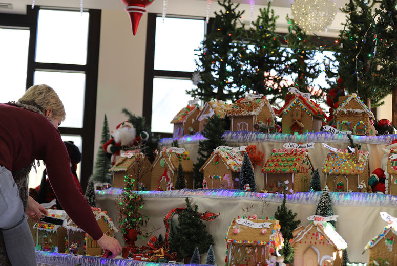Woman sets gingerbread house on large gingerbread village display