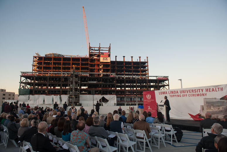 crowd watches beam being put into place