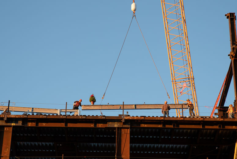 steel beam being put into place by construction workers