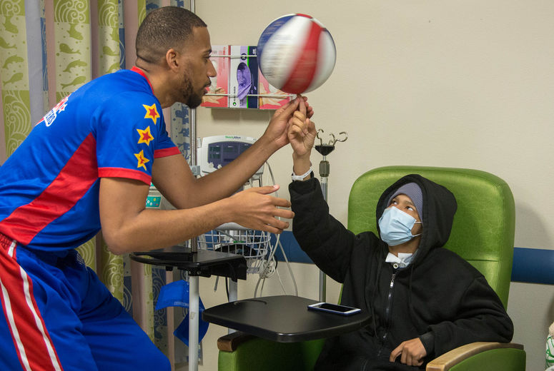man spinning basketball on patients finger