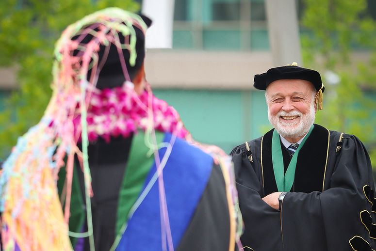 newly graduated student stands covered in silly string in front of laughing university president