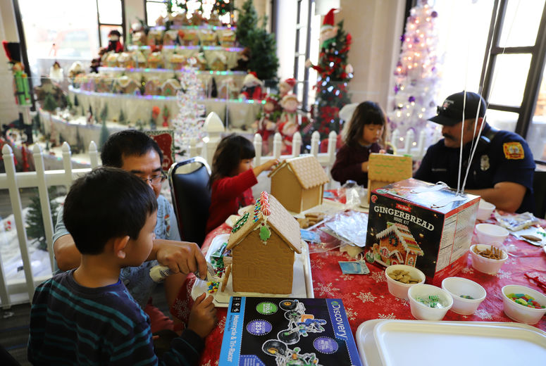 children and adults gather around table while decorating gingerbread houses