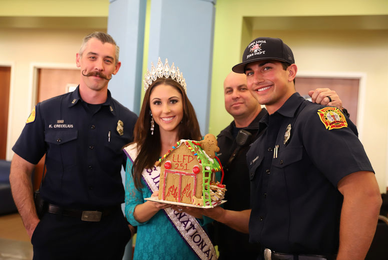 three firemen and a pageant queen pose with a decorated gingerbread house