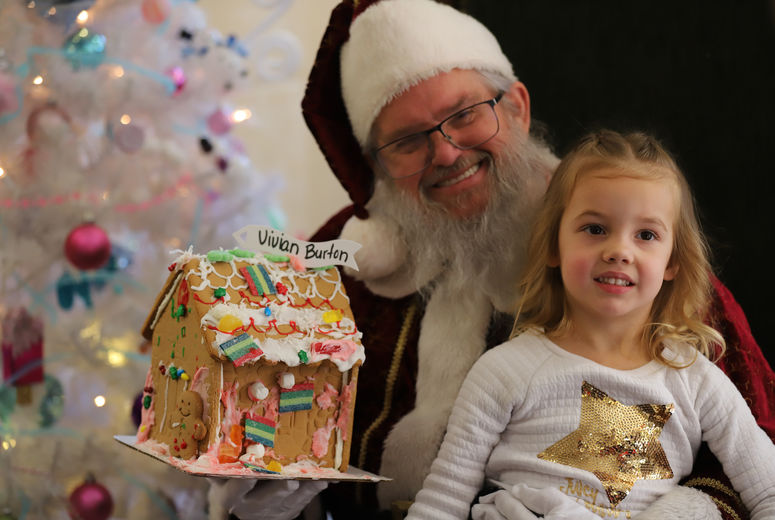 man dressed as Santa Claus poses for a picture with small female child