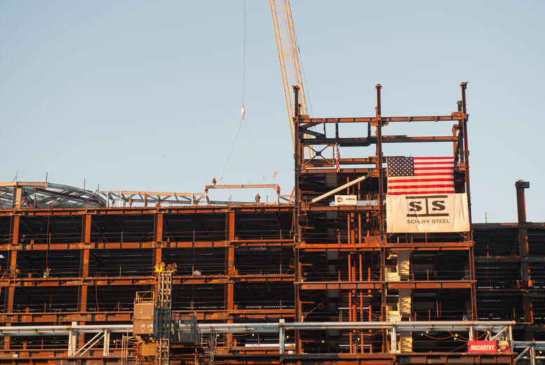 construction crane places ceremonial topping off beam onto steel structure