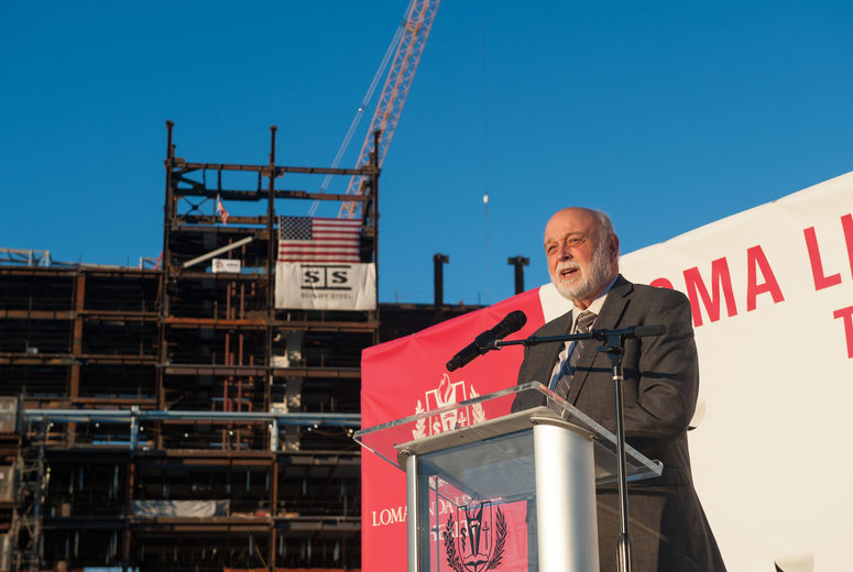 white male speaking at podium in front of construction site