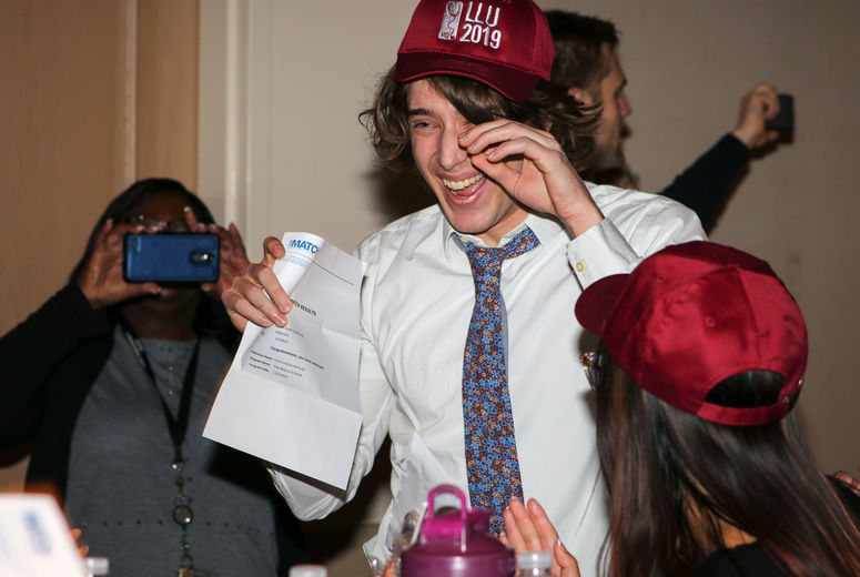 male student holds opened match day envelope while crying tears of joy