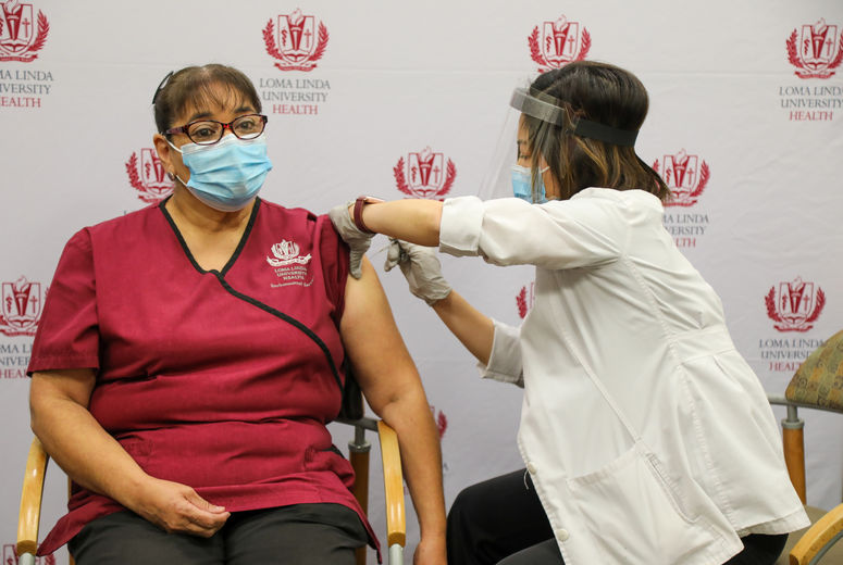 female staff member receives vaccination