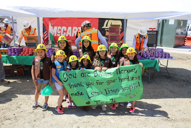group of girl scouts pose with banner thanking construction workers
