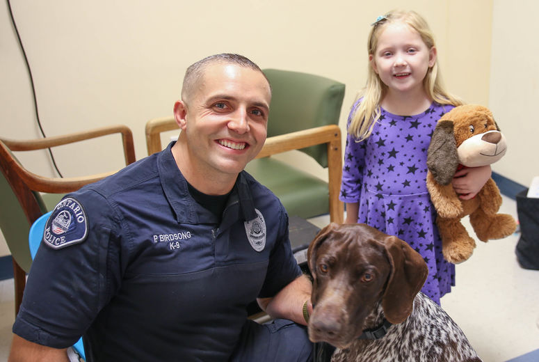 small girl patient poses for picture with officer and dog