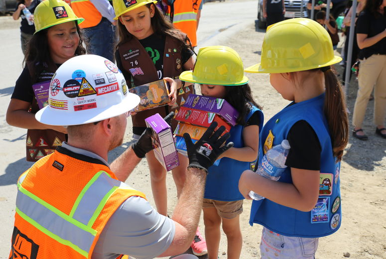 girl scouts try to help construction worker pick a box of cookies