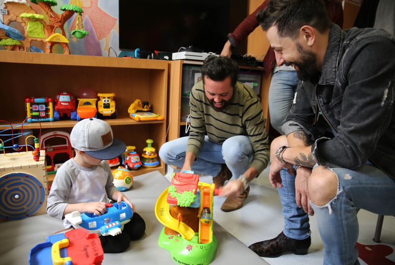 two male members of the band play with toys with a young male patient