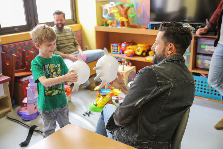 young male patient plays with balloons with male lead singer