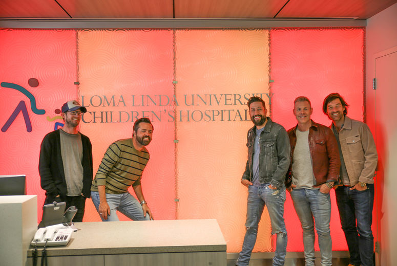 old dominion pose with colorful childrens hospital sign