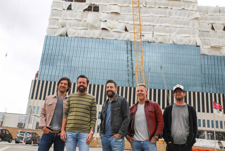 band poses in front of construction site of new hospital towers