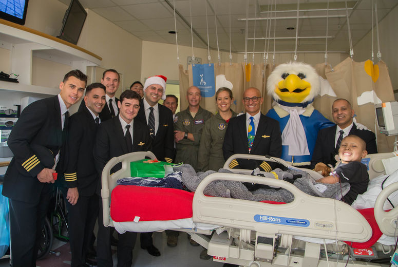 twelve pilots pose for photo with patient