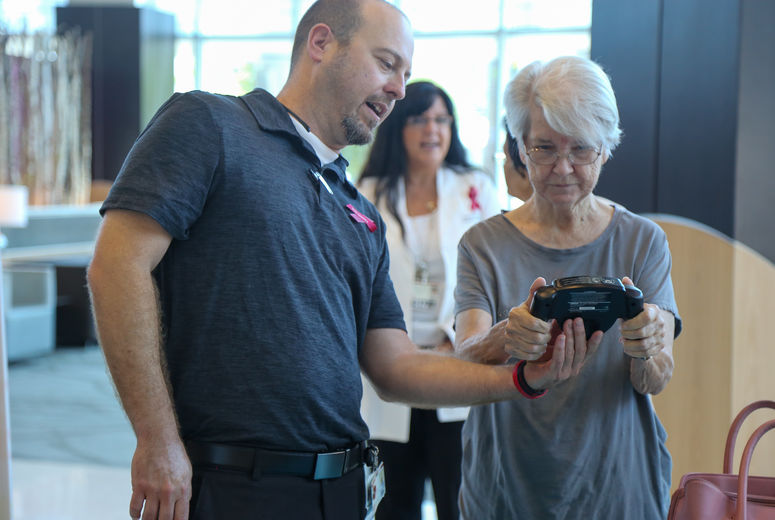 Man helps women hold BMI calculator for testing