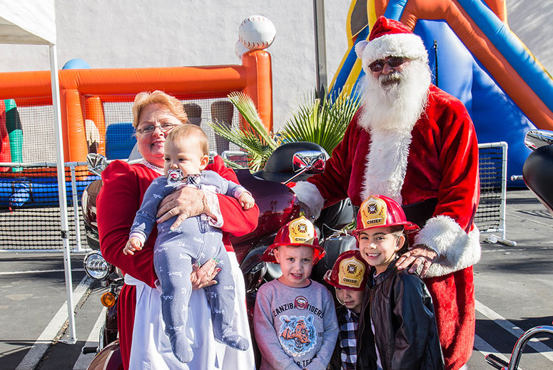 kids pose for picture with Santa and Mrs. Claus