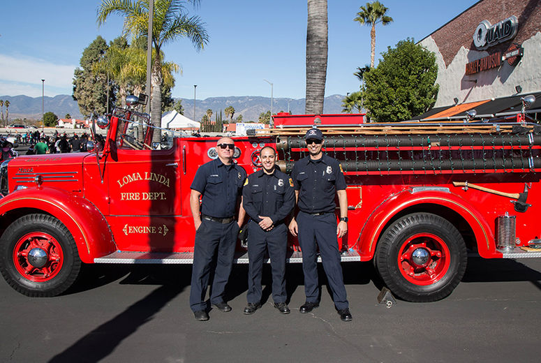 firemen standing with antique fire truck